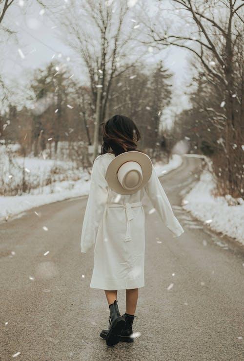 在无叶树附近的沥青路面上的苗条时尚女人