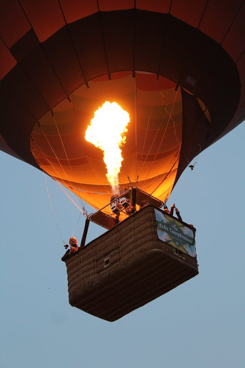 From below of hot air balloon with bright burning flame flying in cloudless evening sky