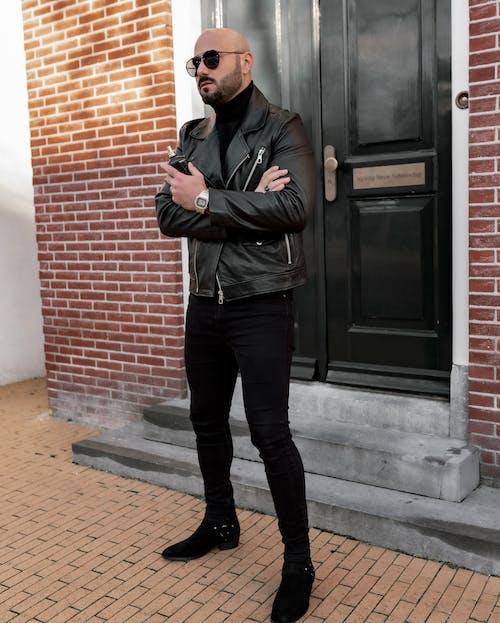 Man in Black Zip Up Jacket and Black Pants Standing Beside Black Wooden Door