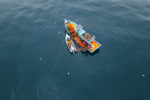 Drone view of boat and vessel moored on rippling sea water during traditional net fishing