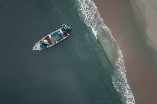 Aerial view of small modern motorboat moored on sandy seacoast near tranquil sea