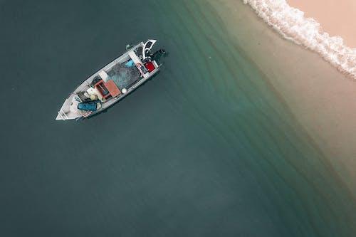 Motorboat moored on seawater near sandy beach