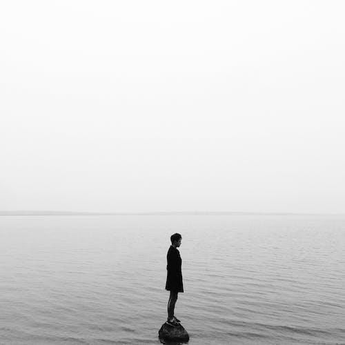 Мужчина в черном пиджаке стоит на берегу моря