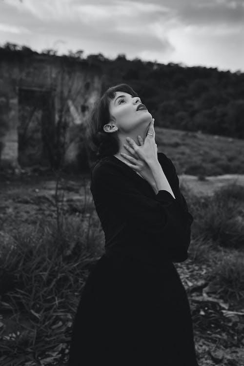 Woman in Black Long Sleeve Shirt Standing on Grass Field