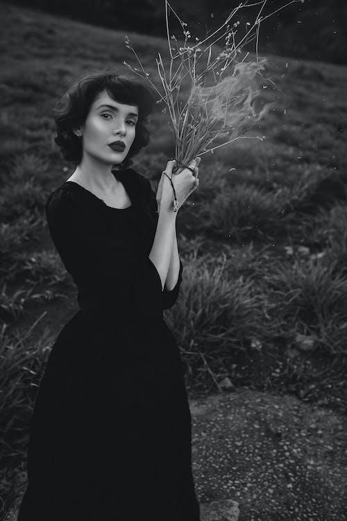 Woman in Black Dress Holding White Dandelion