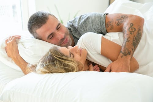 Man in White T-shirt Lying on Bed Hugging Woman in White T-shirt