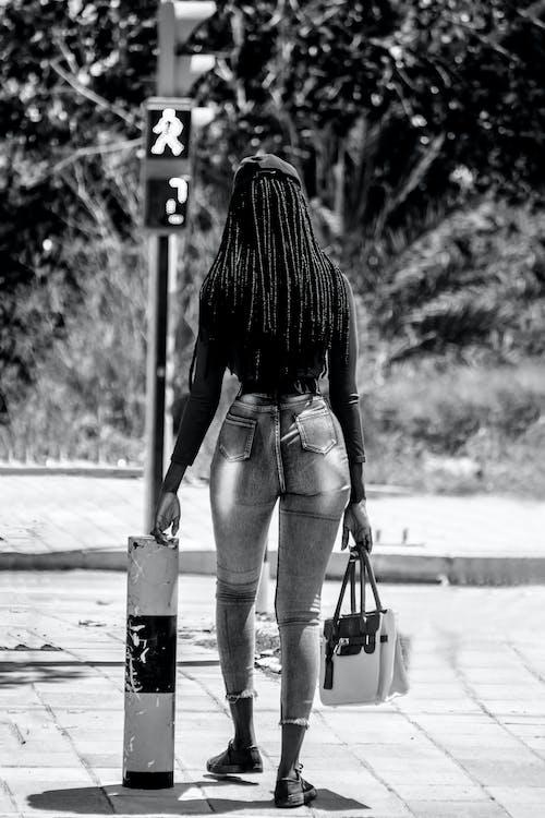 Black woman in stylish jeans walking on street