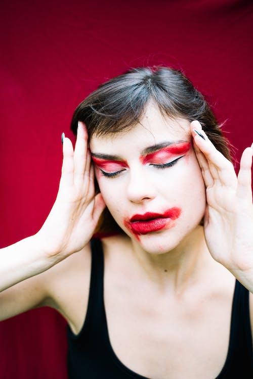 赤い口紅と黒いタンクトップの女性