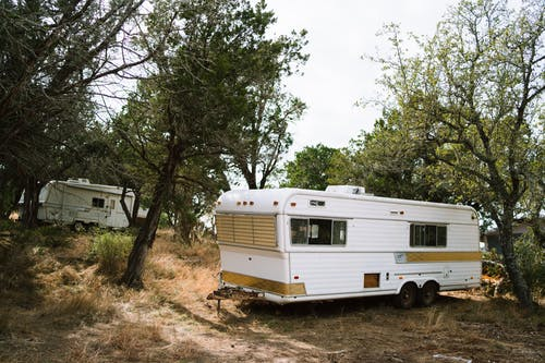 White and Brown Rv Trailer Near Green Trees