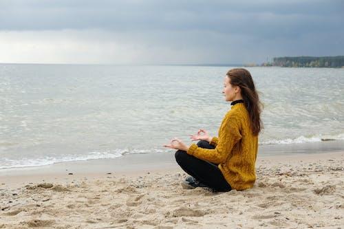 Woman doing yoga on sandy shore near sea