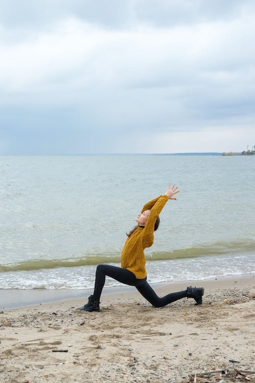 Side view full body of young lady in casual clothes doing Crescent Lunge on sandy shore near sea in daytime under bright cloudy sky