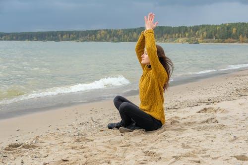 Female meditating on beach near water
