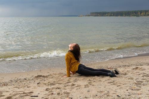 Woman in Black Long Sleeve Shirt and Orange Scarf Sitting on Beach