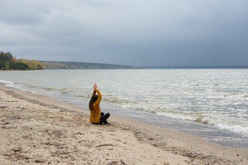 Faceless female meditating near water on beach