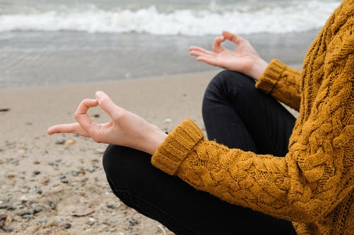 Person in Brown Knit Sweater and Black Pants Sitting on Beach Shore