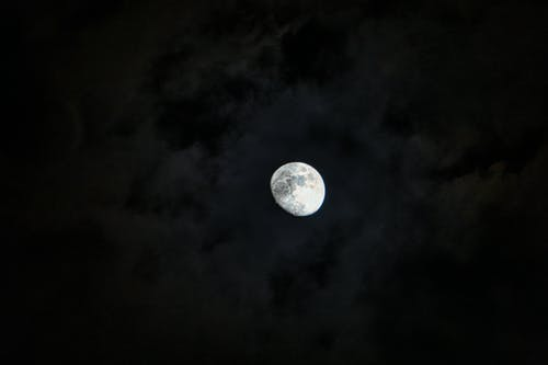 Bright white glimmering majestic moon with gray craters in dark sky with clouds