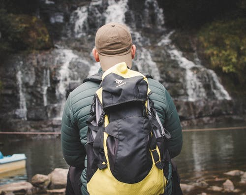 Man in Green Jacket and Yellow Backpack Standing Near River