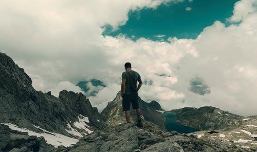 Man in Black T-shirt and Black Pants Standing on Rocky Mountain Under White Clouds during