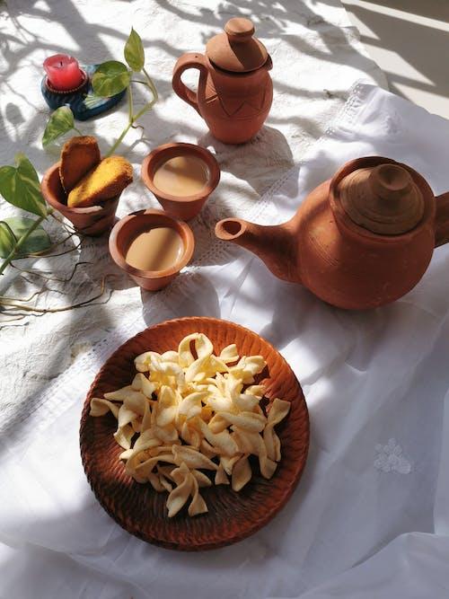 Brown Ceramic Teapot Beside Brown Ceramic Mug on Brown Wooden Round Tray