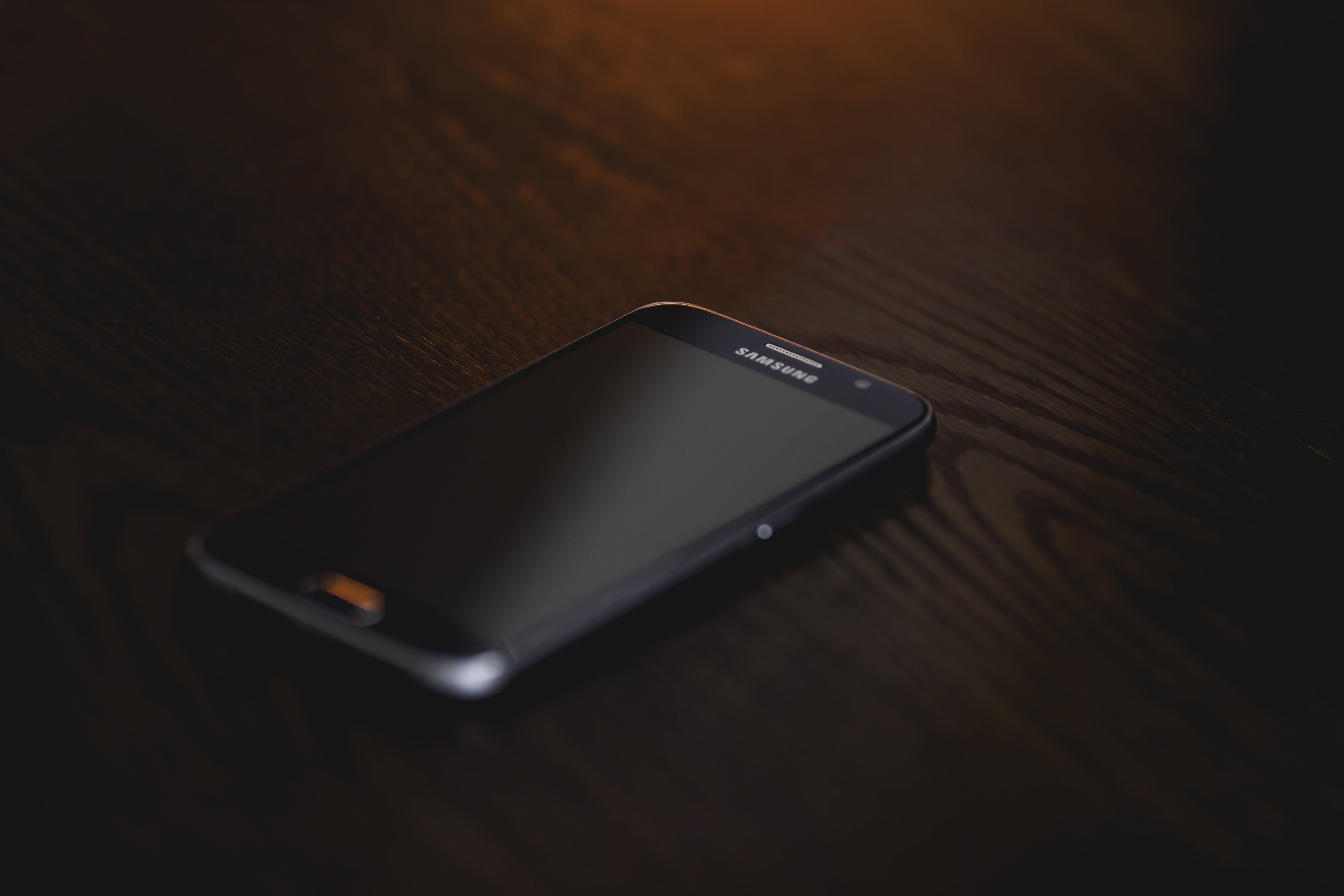 Black Samsung Smartphone at Brown Wooden Surface
