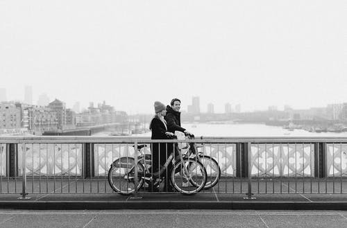 Monochrome Photo of Couple Walking with their Bicycle