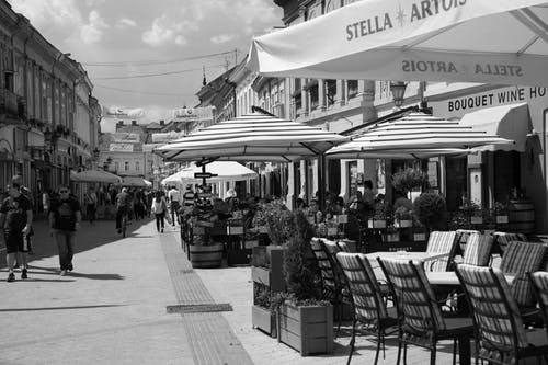 Black and white scenery of pedestrian crowded street with between historical buildings and modern outdoor restaurants with tables under umbrellas on sunny summer day