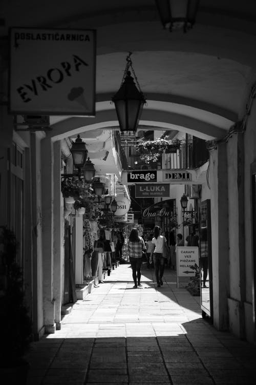 Pedestrian walking on narrow street near arched passage