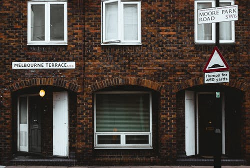 Facade of old brick residential building with plastic windows and jalousie near road with sign