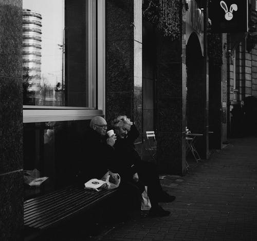 Black and white side view of aged couple sitting on bench on city street and eating and drinking coffee