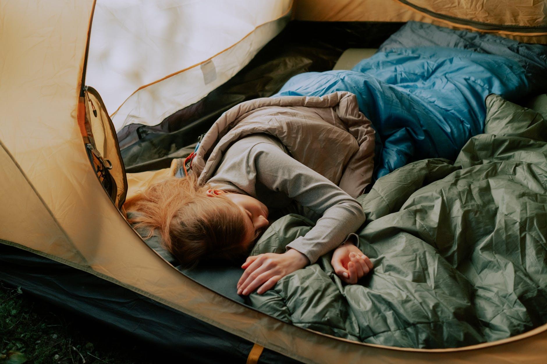 woman sleeping in tent on sleeping pad