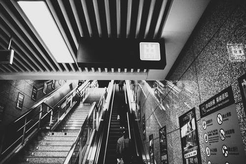 Grayscale Photo of People Walking on Stairs