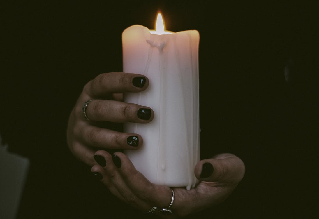 Person Holding White Candle With Fire