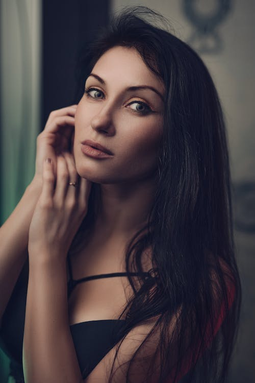 Self assured young lady with long dark hair in elegant lingerie touching face and looking at camera in room