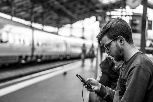 Grayscale and Selective Focus Photography of Man Holding Phone at Train Station