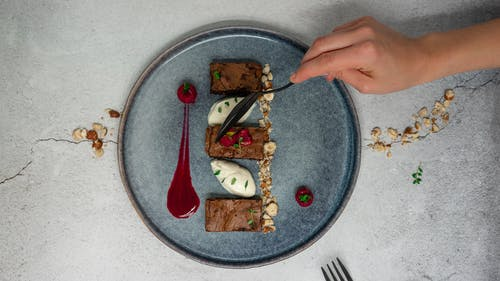 Top view of crop anonymous person holding spoon while eating delicious chocolate dessert from ceramic plate