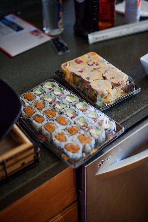 High angle of appetizing sushi in plastic containers on table in cozy kitchen