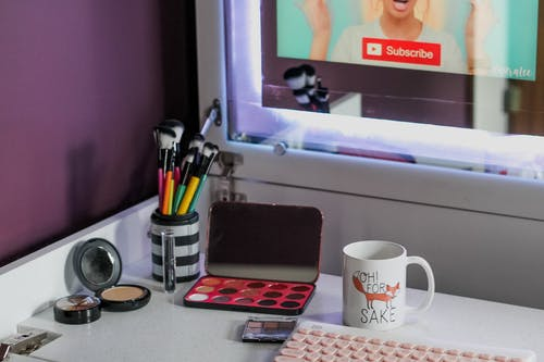 High angle of professional makeup supplies near keyboard and computer on table at home