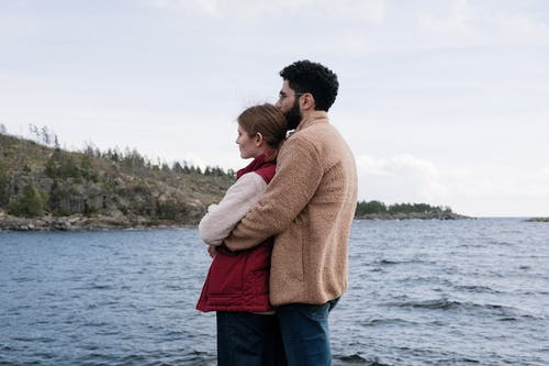 Man in Brown Sweater Carrying Girl in Red Sweater