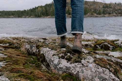 Person in Blue Denim Jeans and Brown Hiking Shoes Standing on Rocky Shore