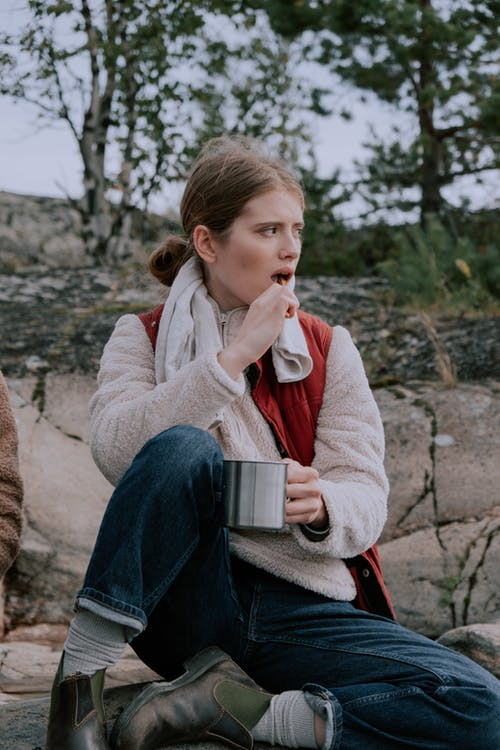 Woman in Gray Jacket Holding White Ceramic Mug