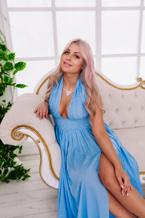 Confident positive young female with long wavy hair in stylish maxi dress with decollete sitting on elegant sofa and smiling at camera