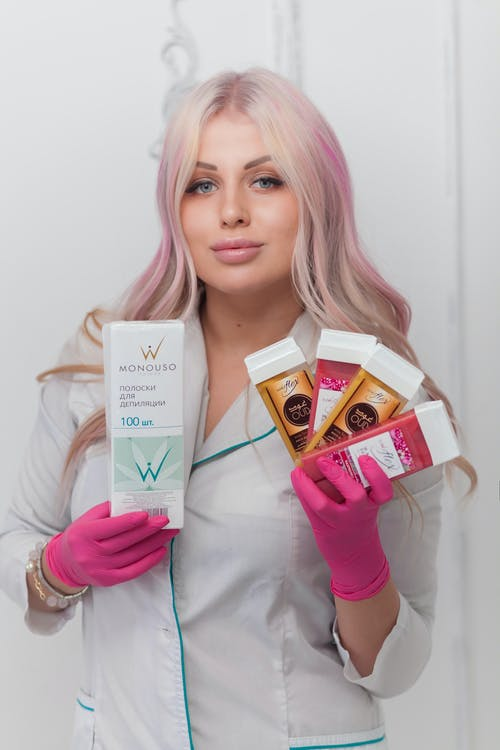 Beautician showing products for depilation in salon