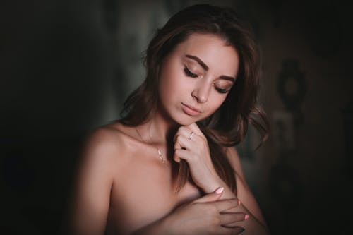 Sensual young woman touching hair with closed eyes in room