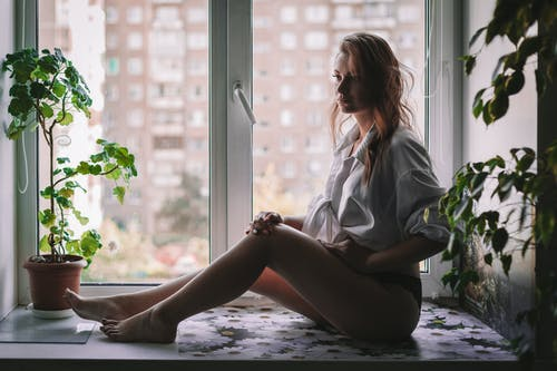 Side view of barefooted dreamy female with long wavy hair in shirt and panties sitting on windowsill and looking away thoughtfully