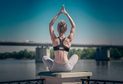 Back view of fit anonymous female with namaste gesture sitting in Padmasana on waterfront during meditation