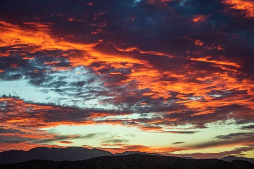 Silhouette of Mountains Under Orange and Blue Cloudy Sky during Sunset