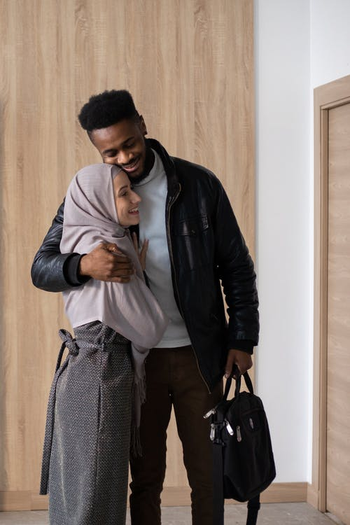 Loving smiling multiethnic couple in casual outfits embracing each other near door at home