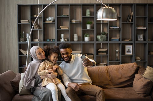 Delighted multiethnic family taking selfie sitting on couch