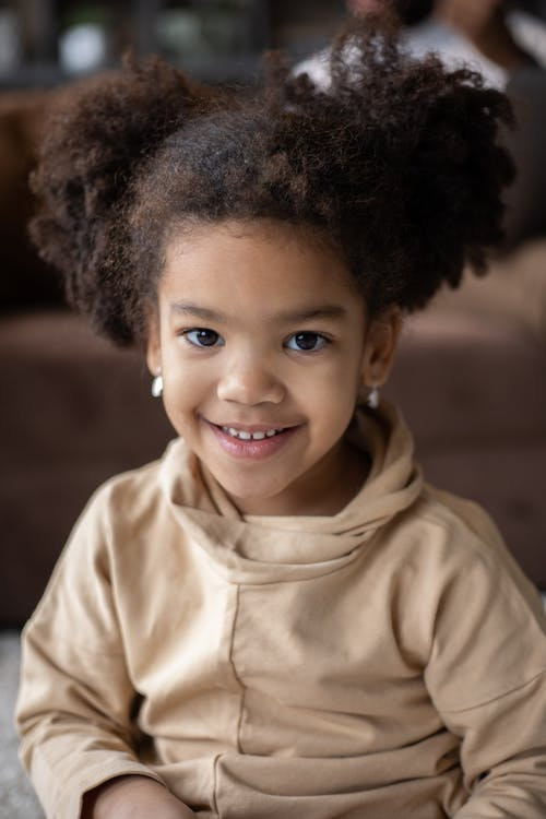 Adorable happy African American little girl in casual wear with earrings looking at camera