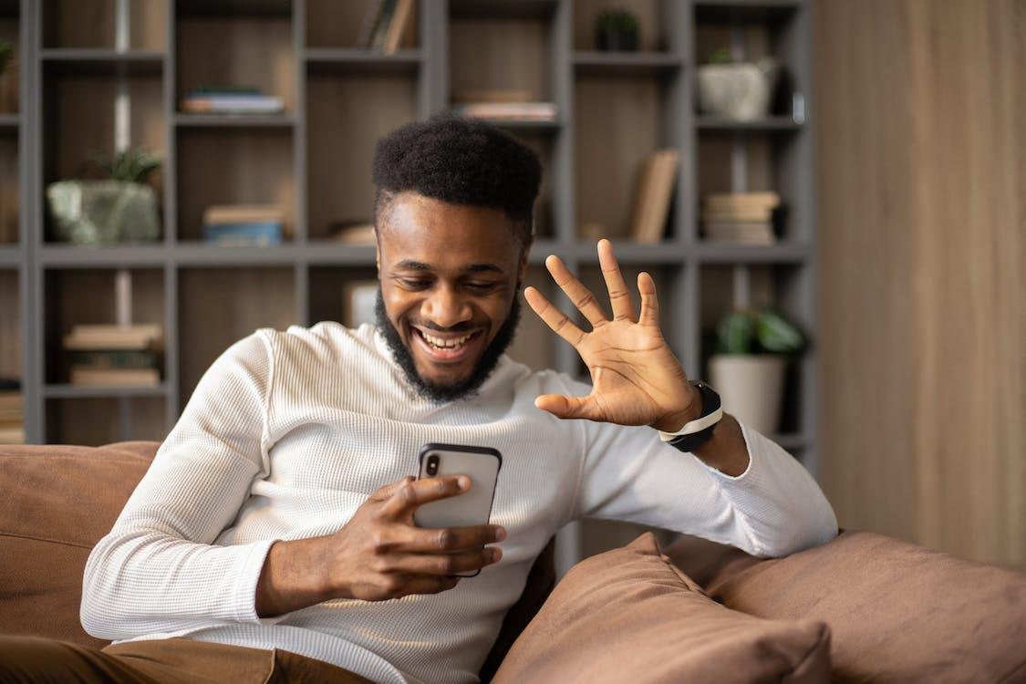 Cheerful black man having video call and waving hand